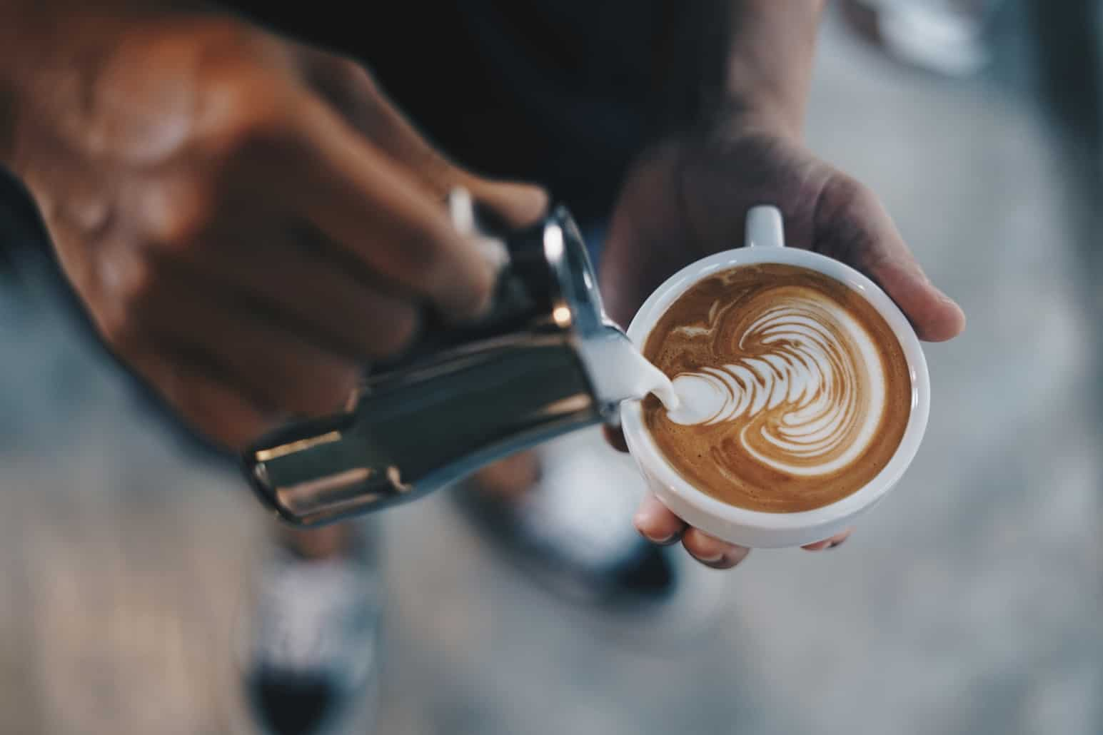 Low Section Of Person Pouring Milk In Cappuccino