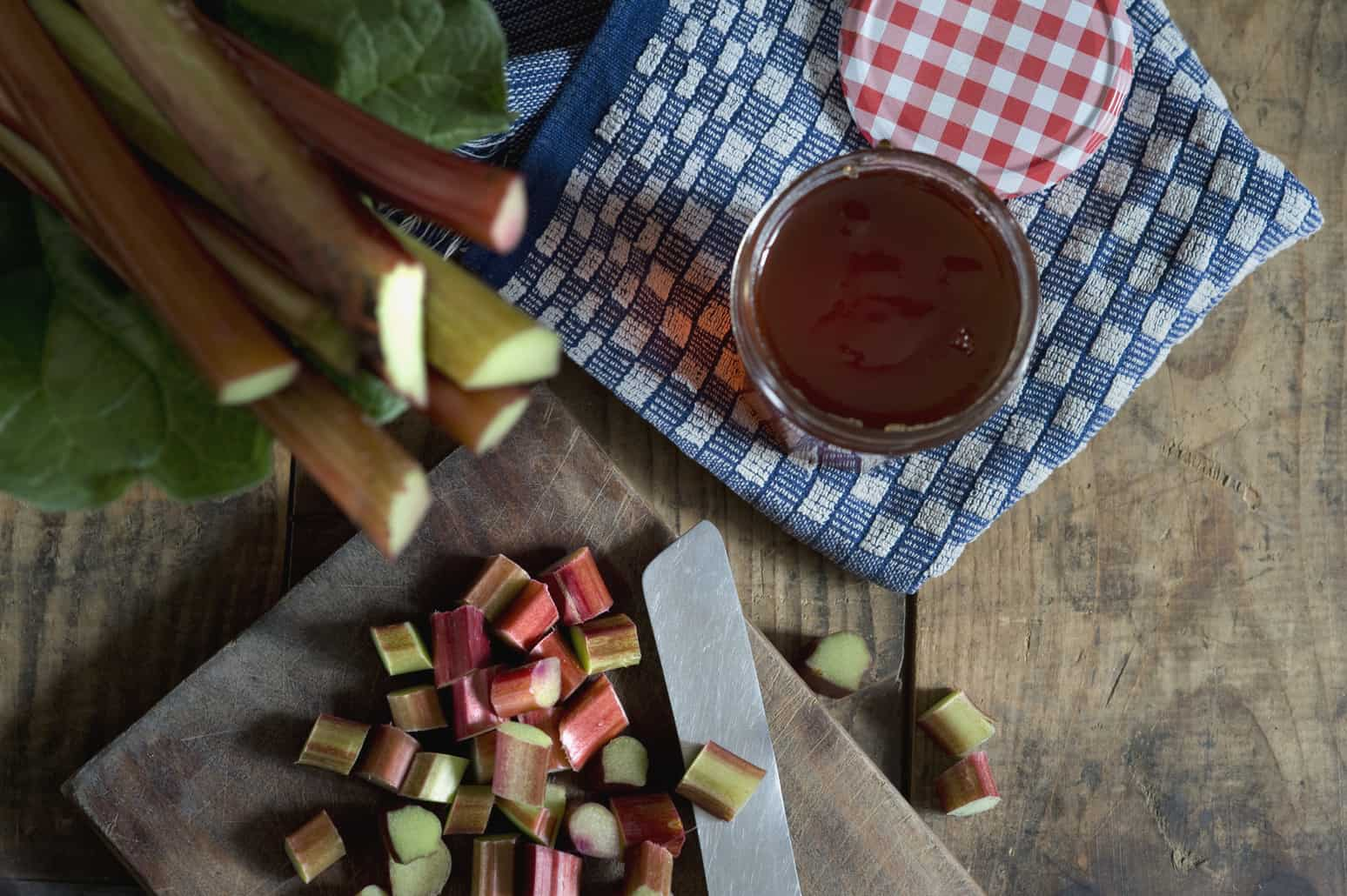 Sliced And Whole Rhubarb And Jam Jar Of Rhubarb Jelly On Wood, Elevated View