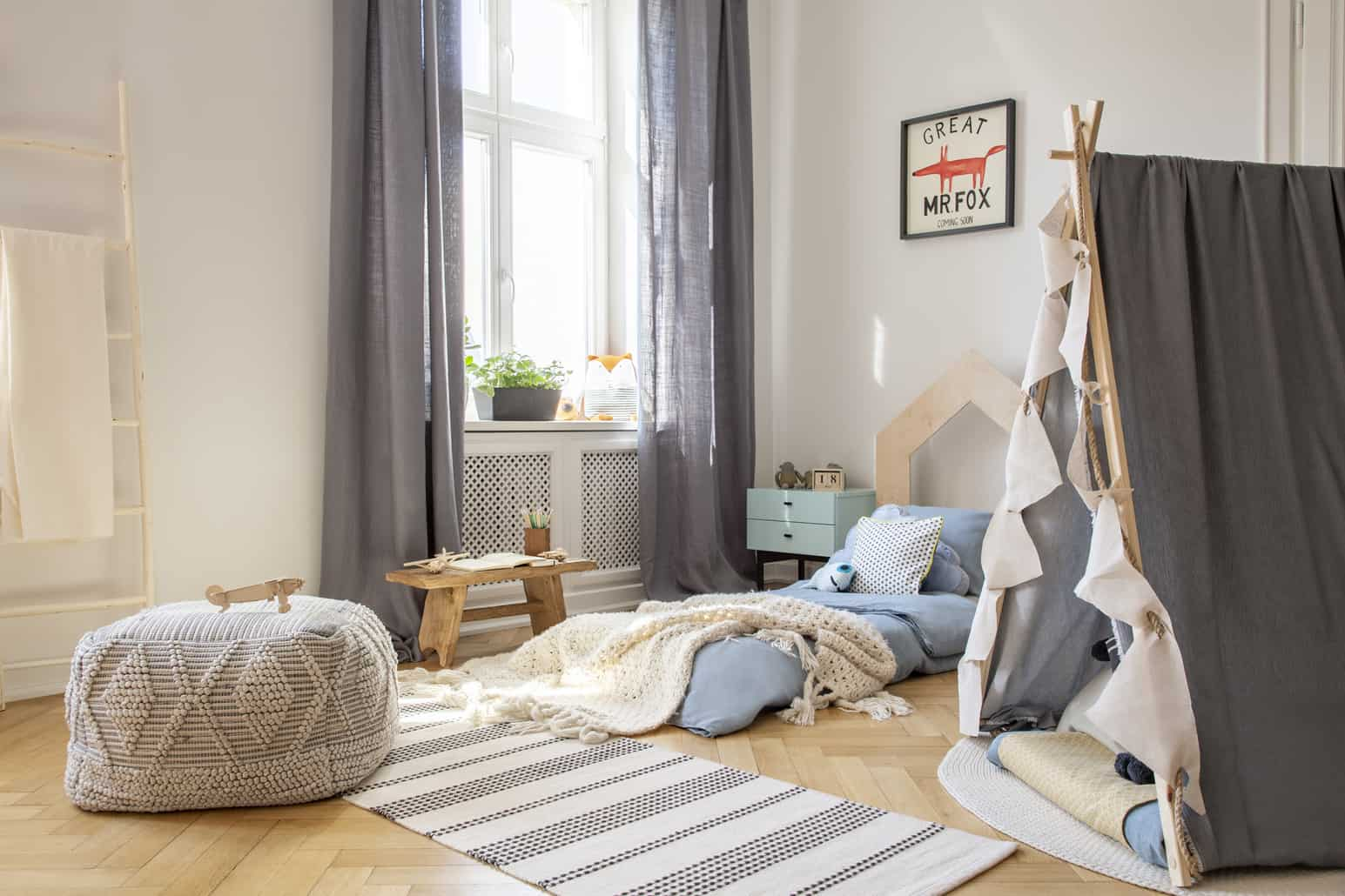 pouf and tent in bright kid's bedroom interior with drapes at window and blanket on blue bed. real photo