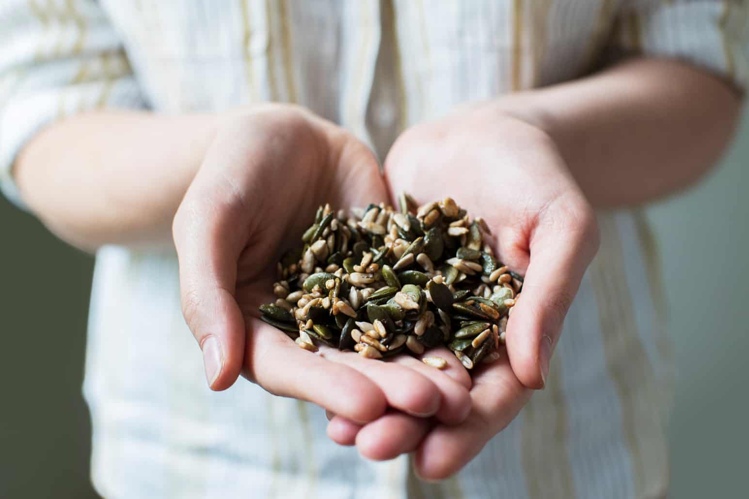close up of woman holding handful of healthy seeds