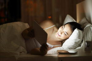 woman watching tv in a tablet on the bed in the night